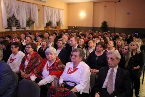 Zdjęcie przedstawia siedzących ludzi podczas spotkania opłatkowego.