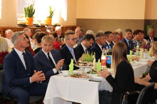 Zdjęcie przedstawia zespół ludowy, oficjeli i innych ludzi siedzących przy stołach.