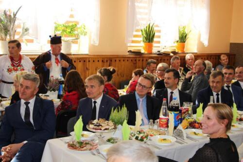 Zdjęcie przedstawia siedzących oficjeli przy stołach.