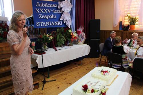 Zdjęcie przedstawia kobietę która mówi do mikrofonu a w tle widać innych ludzi.