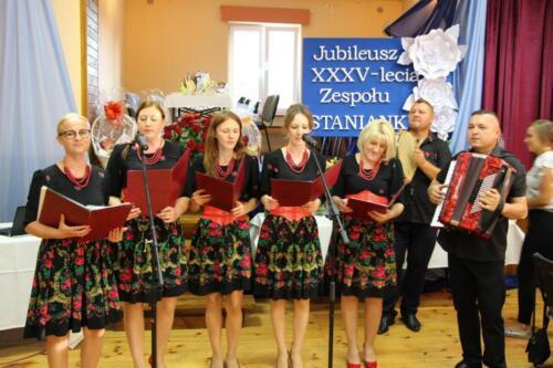 Zdjęcie przedstawia zespół ludowy wykonujący swój utwór.