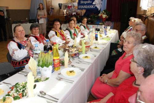 Zdjęcie przedstawia zespół ludowy i innych ludzi siedzących przy stołach.