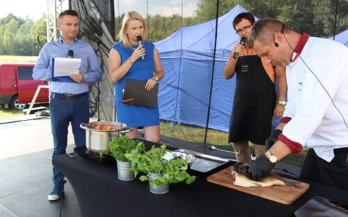 Obrazek przedstawia kucharza których filetuje karpia.