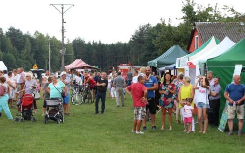 Obrazek przedstawia ludzi biorących udział w festynie.