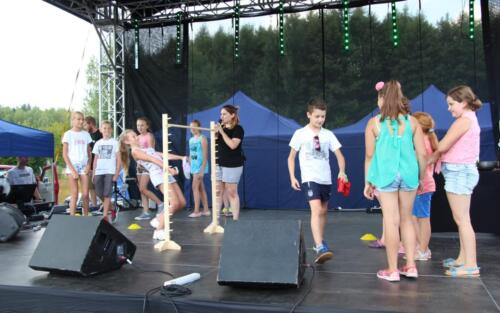 Obrazek przedstawia ludzi biorących udział w zawodach na festynie.