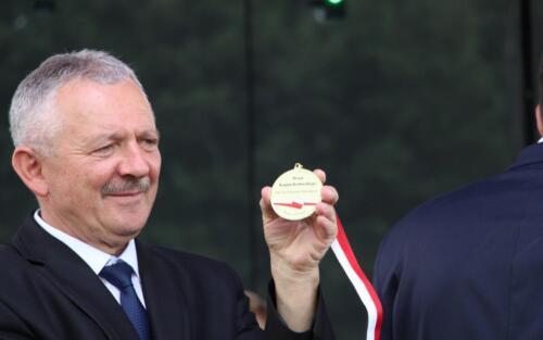 Obrazek przedstawia człowieka który trzyma medal w ręce.