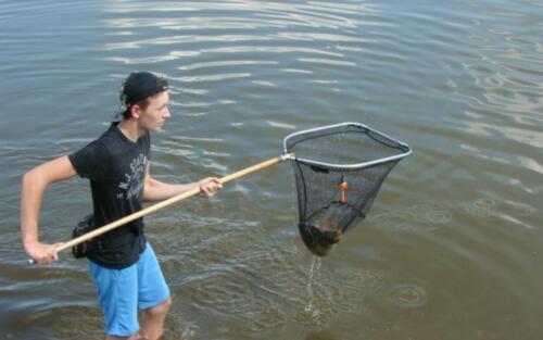 Obrazek przedstawia człowieka wyciągającego rybę z wody.