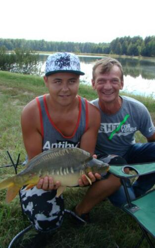Obrazek przedstawia dwóch mężczyzn pozujących do zdjęcia z rybą.