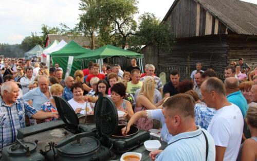 Obrazek przedstawia ludzi w kolejce po ciepły posiłek.