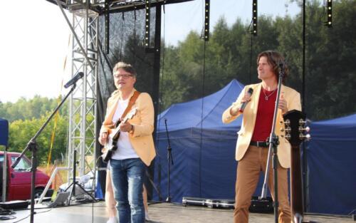 Obraz przedstawia ludzi grających na scenie.
