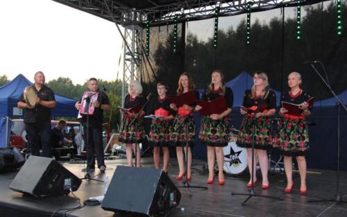 Obraz przedstawia zespół ludowy na scenie.