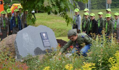 Zdjęcie przedstawia ludzi stojących przy kamieniu upamiętniającym.