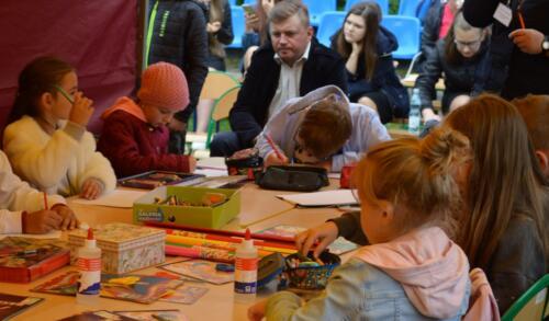 Zdjęcie przedstawia dzieci które coś malują, w tle widać ludzi.