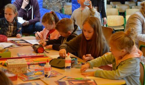 Zdjęcie przedstawia dzieci które coś malują, w tle widać ludzi