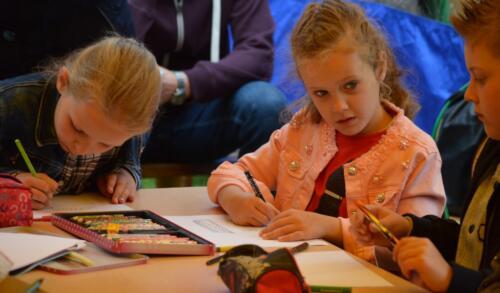 Zdjęcie przedstawia dzieci które coś malują.