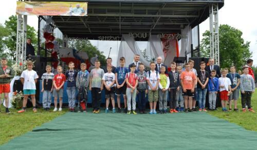 Zdjęcie przedstawia ludzi stojących przy scenie.