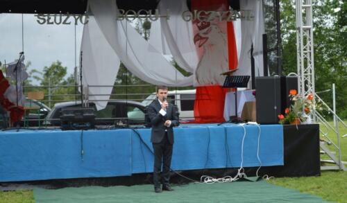 Zdjęcie przedstawia człowieka stojącego przy scenie.