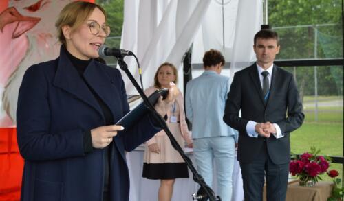 Zdjęcie przedstawia kobietę która śpiewa oraz innych ludzi na scenie.