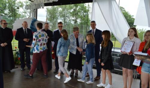 Zdjęcie przedstawia ludzi na scenie którzy odbierają gratulacje.