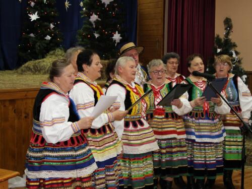 Zdjęcie przedstawia zespół ludowy na scenie.