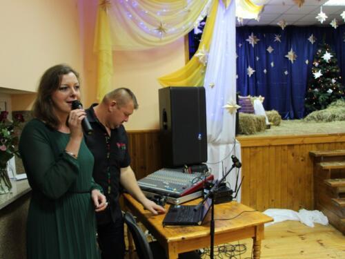 Zdjęcie przedstawia kobietę która śpiewa na scenie.