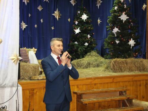 Zdjęcie przedstawia człowieka mówiącego do mikrofonu