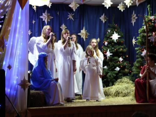 Zdjęcie przedstawia ludzi odgrywających scenkę bożonarodzeniową.