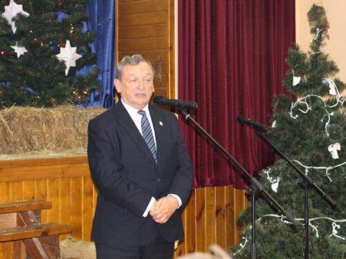 Zdjęcie przedstawia człowieka który mówi do mikrofonu.