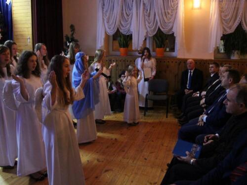 Zdjęcie przedstawia ludzi którzy odgrywają scenkę bożonarodzeniową.