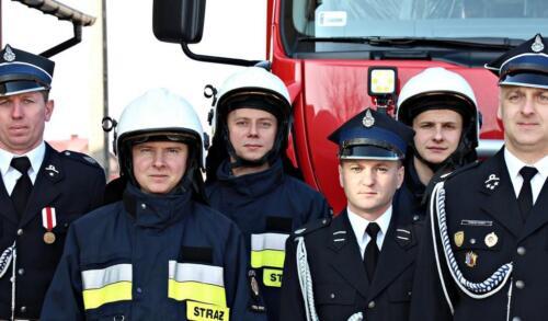 Zdjęcie przedstawia ludzi i strażaków pozujących do zdjęcia na uroczystym przekazaniu wozu strażackiego dla gminy Potok-Stany na tle tego pojazdu.