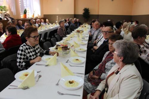 Obrazek przedstawia siedzących ludzi przy stole.