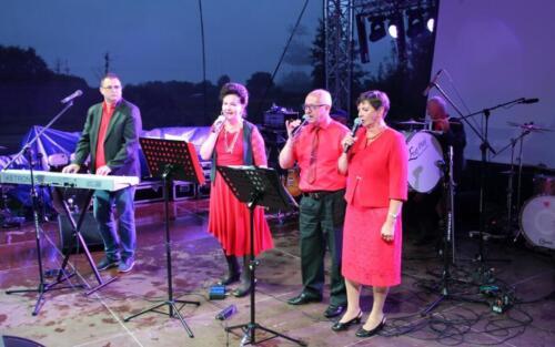 Zdjęcie przedstawia grupę osób  stojących na scenie i śpiewających przez mikrofon