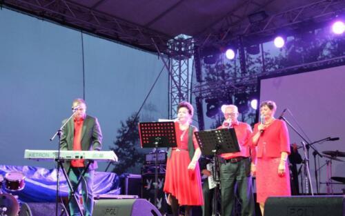 Zdjęcie przedstawia grupę osób śpiewających piosenkę na scenie