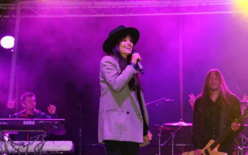 Zdjęcie przedstawia śpiewającą na scenie kobietę