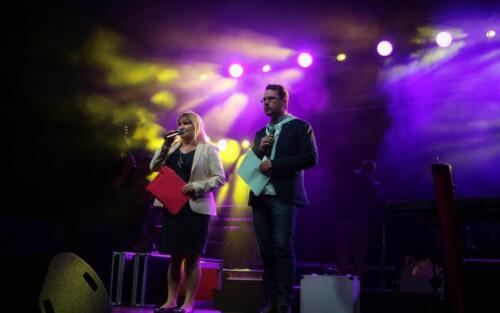 Zdjęcie przedstawia dwóch osób stojących na scenie i mówiących przez mikrofon