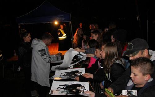 Zdjęcie przedstawia grupę ludzi stojących w kolejce za autografem