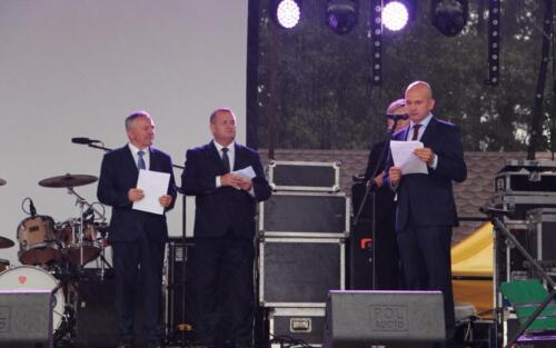 Zdjęcie przedstawia grupę ludzi mówiących przez mikrofon na scenie