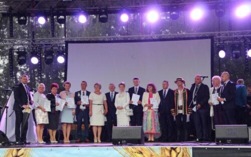 Zdjęcie przedstawia grupę osób  stojących na scenie i mówiących przez mikrofon